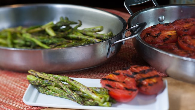 Grilled tomatoes and asparagus on a plate and, in the background, a pan with grilled tomatoes and a pan with grilled asparagus