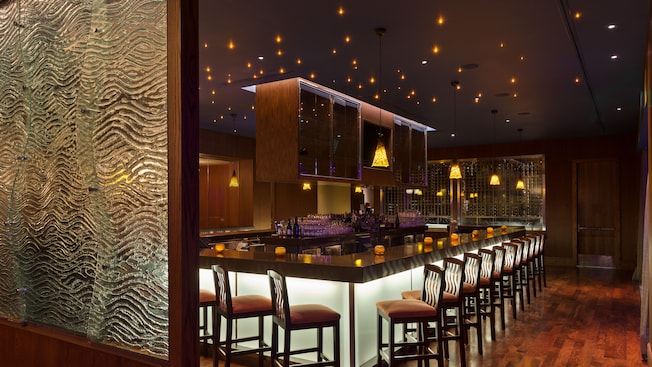 Sleek wooden bar with stools and twinkling ceiling lights above