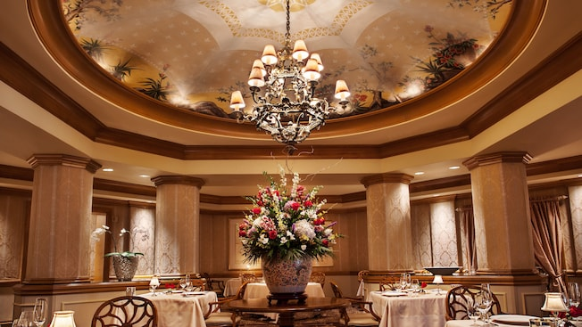 Formal dining room with a crystal chandelier and large bouquet of flowers in the middle