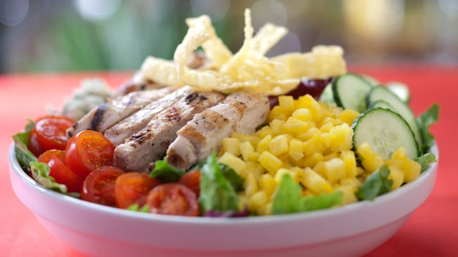 A colorful salad of cherry tomatoes, corn, cucumbers and grilled chicken