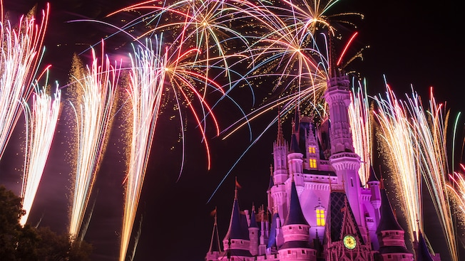 Fireworks burst above and to the sides of Cinderella Castle during Wishes Nighttime Spectacular