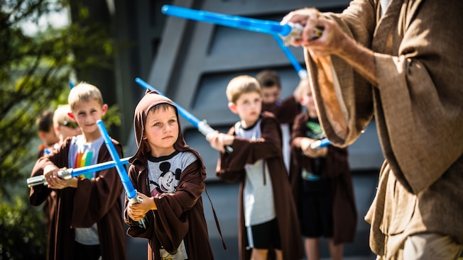 Children wield lightsabers while under the supervision of a Jedi Master.
