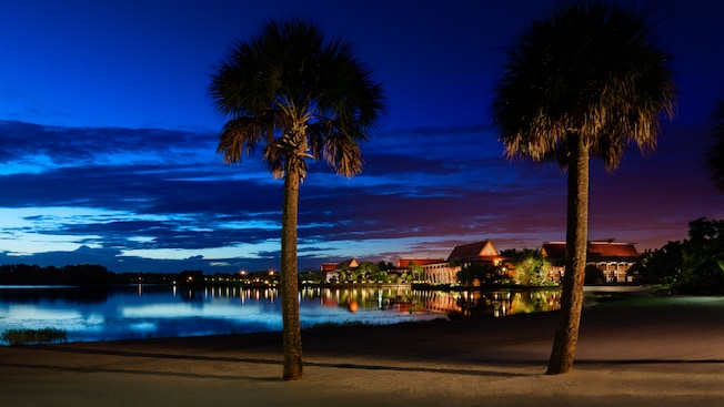 Nighttime view of Disney's Polynesian Resort seen from a nearby beach