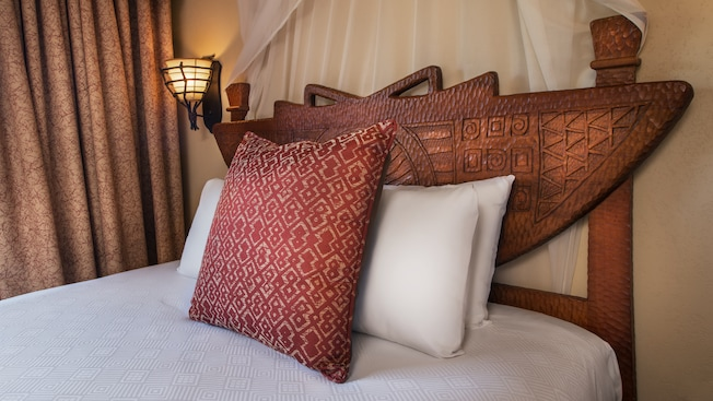 Carved wood and curtained bed headboard with decorative pillows, wall sconce