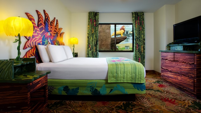A queen bed with a Zazu headboard and end tables across from a TV-dresser and next to a window