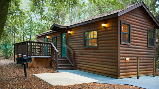A log cabin with a walk path to the steps leading to the porch and front door