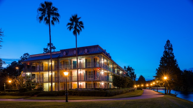 The 3-story accommodations at Disney's Port Orleans Resort – French Quarter, lit up at night