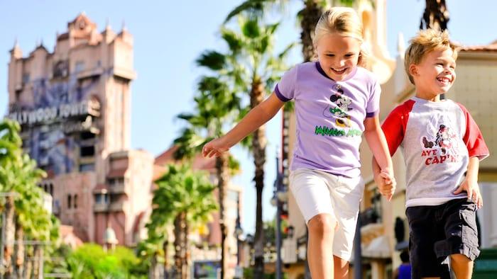 Una niña y un niñosaltande la mano por una calle del Parque Temático Disney's Hollywood Studios