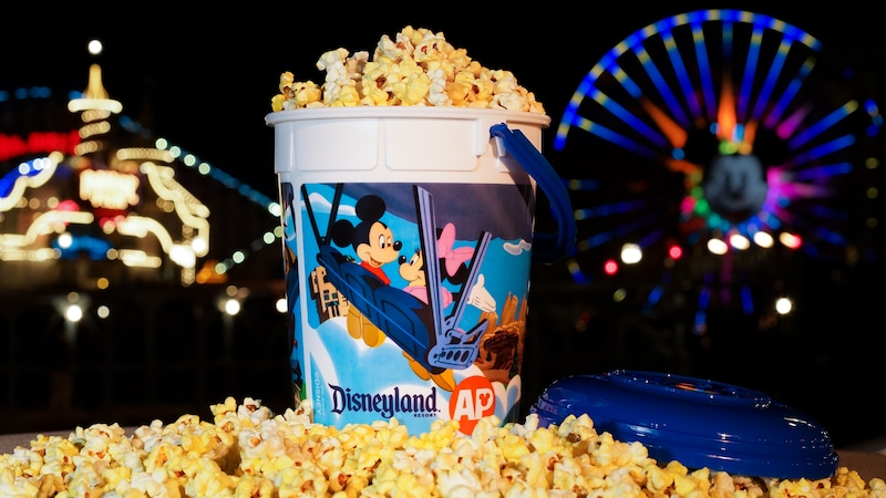 A refillable souvenir bucket featuring Disneyland AP art sits in popcorn