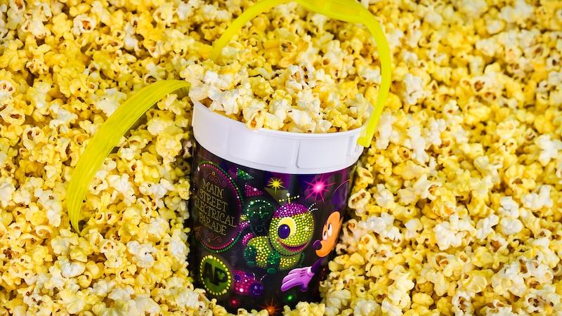 A refillable souvenir bucket featuring Disneyland's Summer Program art sits in popcorn
