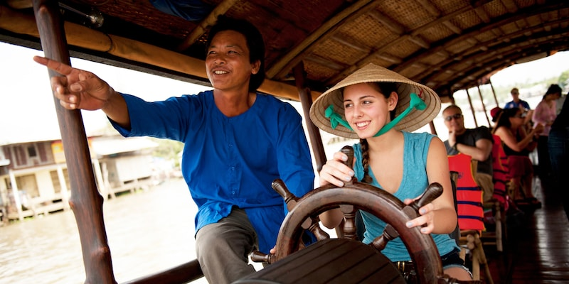 The driver of a roofed touring boat cruising on a river lets a female tourist take the wheel