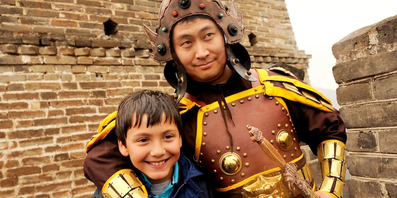 A costumed Chinese warrior and a little boy on top of the Great Wall of China