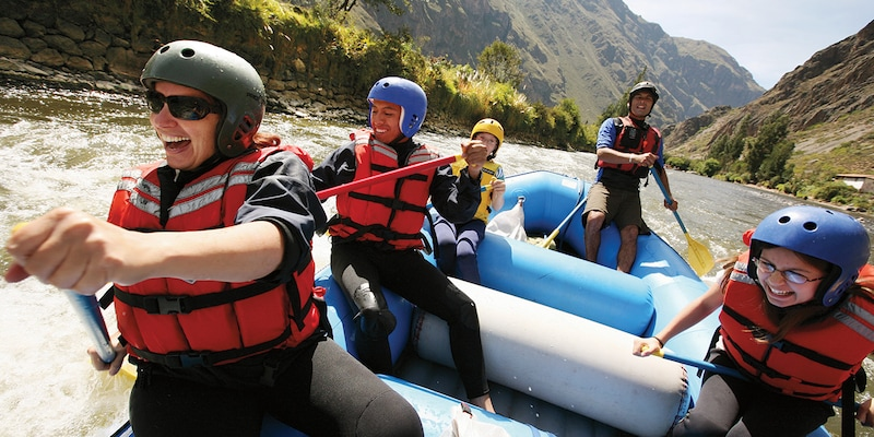 A family wearing athletic helmets rafts down a river