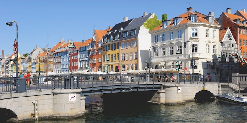 A bridge over a waterway with European buildings on one side