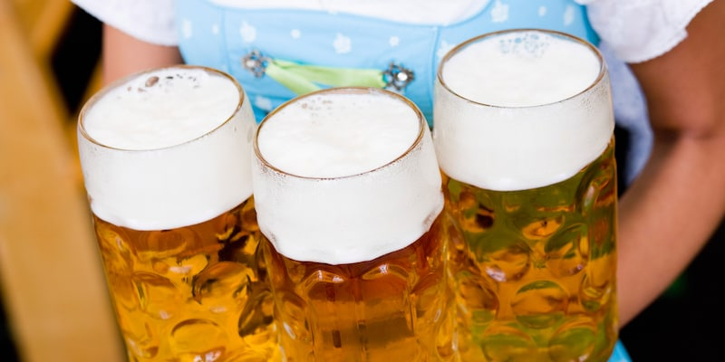 3 glass steins of beer on a tray