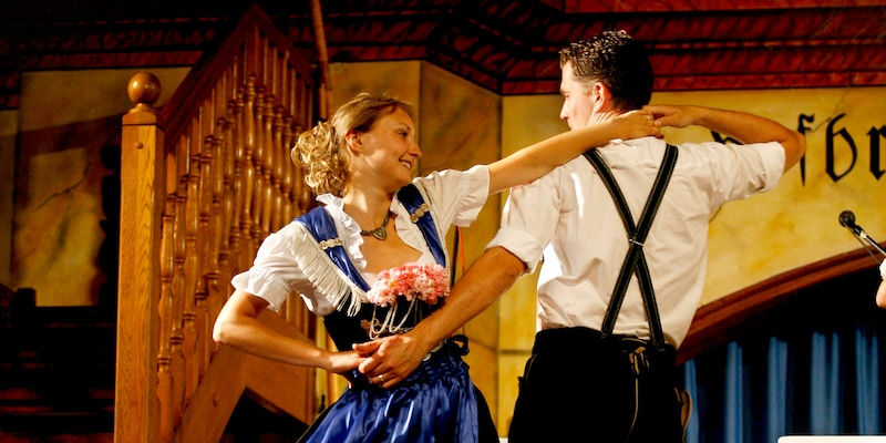 A couple of folk dancers, dressed in traditional German costumes, perform