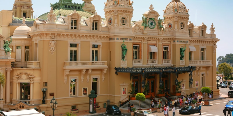 An ornate building adorned with turrets, alcoves, statues, a clock and an awning covering its entry
