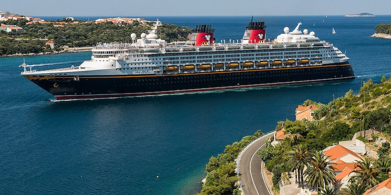 The <i>Disney Magic</i> Cruise Ship sails between two pieces of land with sail boats sailing in the distance