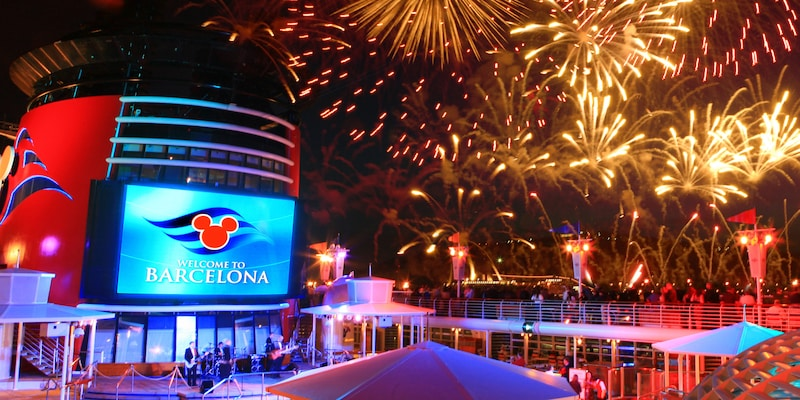 Fireworks over the deck of the Disney Magic® Ship and a sign reading 'Welcome to Barcelona'