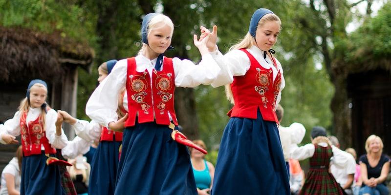 4 Norwegian girls dressed in traditional costumes folk dance