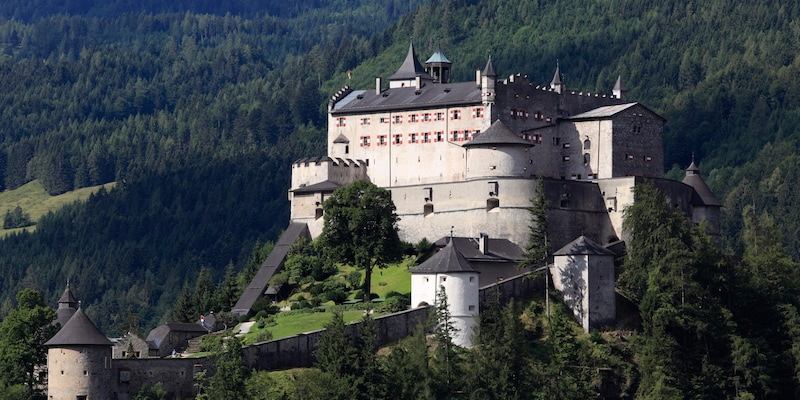 A castle on a hill surrounded by forest with a large, walled yard and guard towers
