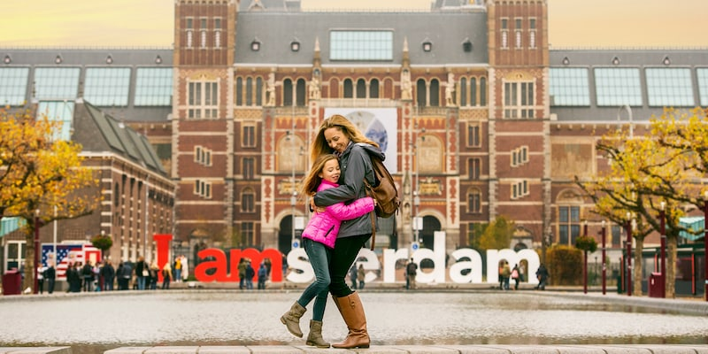 A mother and daughter hug in a square outside a brick building with a sign reading 'I Amsterdam'
