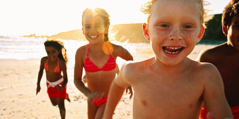 Several kids run along a sunny beach