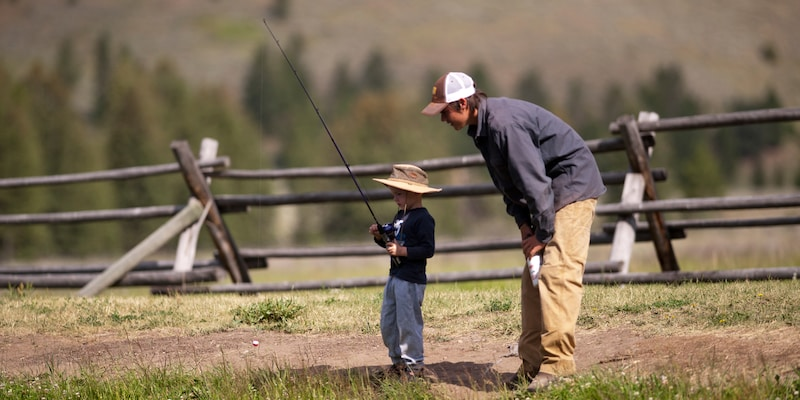 A man watches a boy fishing