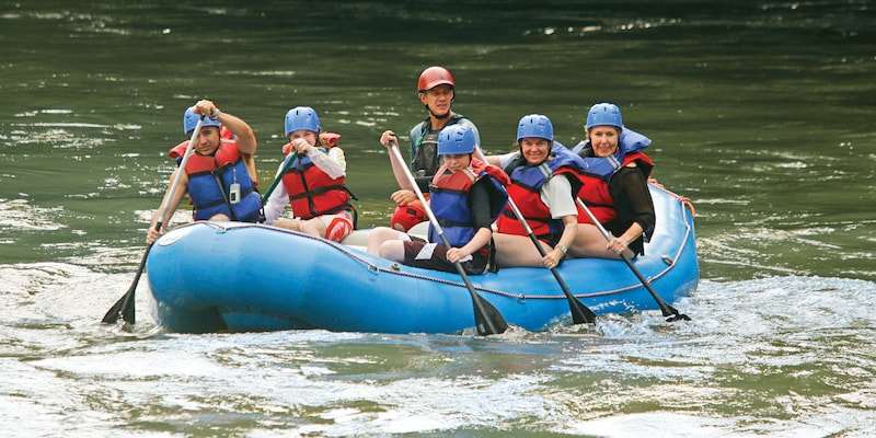 6 people wearing athletic helmets paddle down a river in a raft