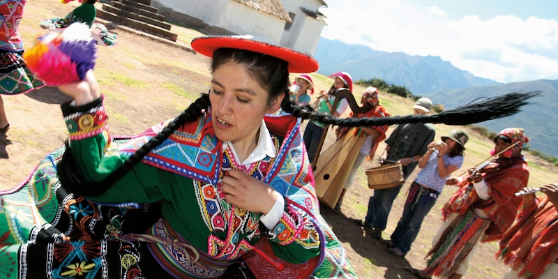 A woman wearing a traditional costume dances while a traditional band plays