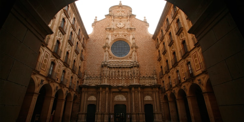 A view of the Santa Maria de Montserrat Abbey façade with its clock, round window and statues of the disciples
