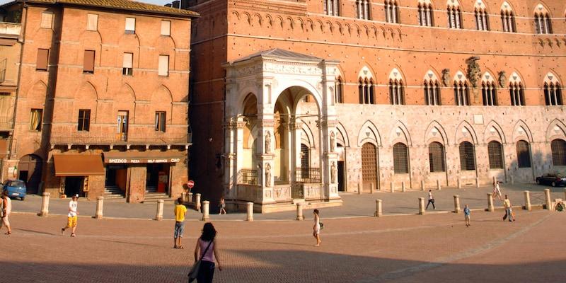 People walk down a street in Siena, Italy