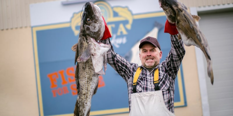 """A smiling man wearing a cap and apron holds 2 large fish in front of a sign that reads, """"EKTA Fiskus: Fish for Sale"""""""