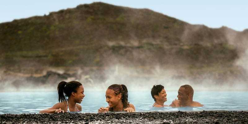 4 people enjoy soaking in the steamy waters of a natural bath