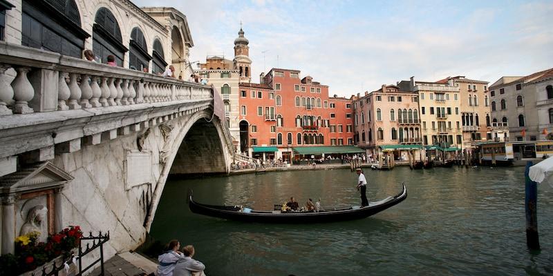 A gondola glides under a bridge in Venice, Italy