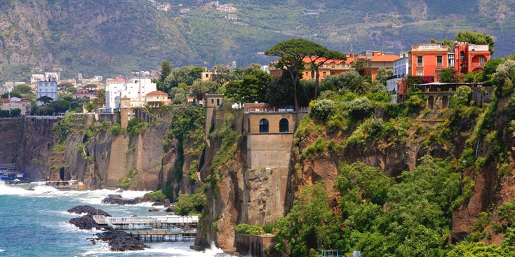 Buildings line steep cliffs that overlook a sea