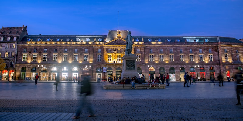 Kléber Square in Strasbourg, France lit up at night with people gathered around the statue of Kléber