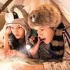 Deux enfants portant des chapeaux de fantaisie inspirés de l'Ouest lisent une carte avec une lampe de poche et une petite lanterne sous un tipi improvisé sur le lit de leur chambre d'hôtel