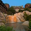 Un arroyo cuyas cascadas bajan por las rocas del patio de Disney's Wilderness Lodge