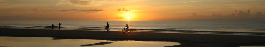 Sun sets over the ocean as 2 Guests ride bikes along a beach and 2 others play at water's edge