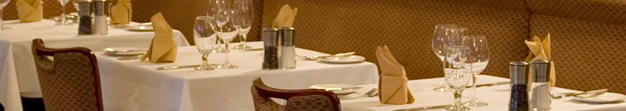 Formally set tables with tableclothes, napkins, silverware and wine glasses