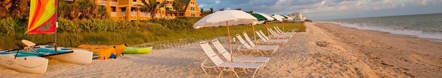 A beach with lounge chairs, umbrellas and rental boats, with the Resort behind