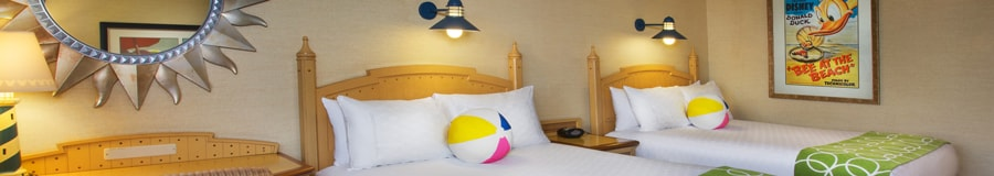 A queen bed with a beach ball-style pillow, writing desk and, beyond, an easy chair and a window