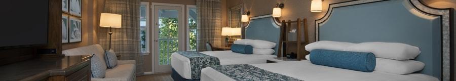 Duas camas queen, uma escrivaninha, cômoda de TV, sofá-cama e, ao fundo, uma sacada