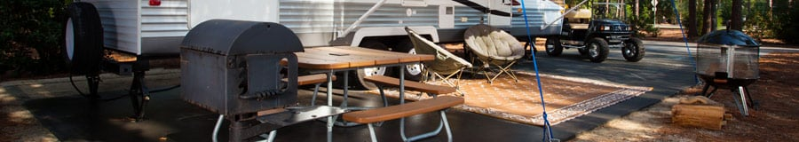 A picnic table next to a BBQ stove and an RV