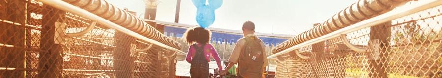 A irmã mais nova com um balão com orelhas do Mickey segura a mão do irmão ao cruzar uma ponte
