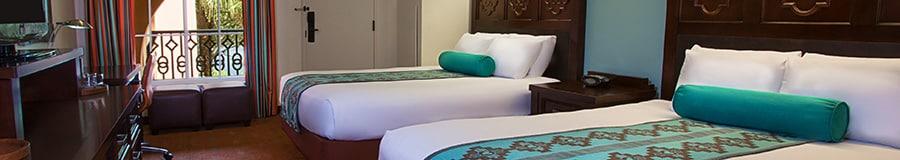 Una cama Queen Size frente a un escritorio con una silla