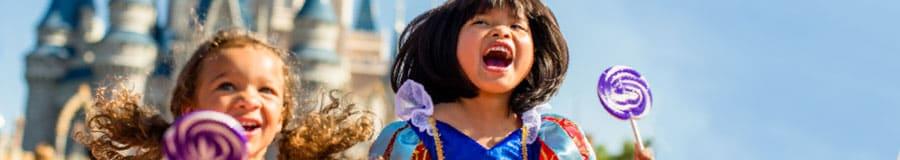 Deux petites filles en costumes de princesse tiennent de grosses sucettes en moulin à vent près du Cinderella Castle