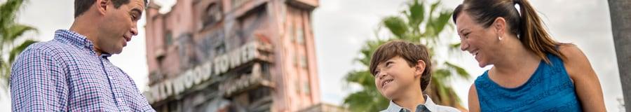 Una niña toma a su padre de la mano con entusiasmo mientras su hermano mayor observa en frente de la Twilight Zone Tower of Terror