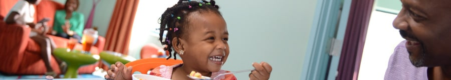 A smiling little girl holds up a spoon of cereal and gazes at her father